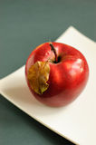 Apple with autumn leaves. Red apple with autumn leaves on a white plate Stock Image