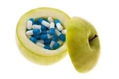 Apple avec des capsules de tablettes. Photographie stock