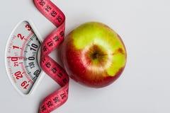 Apple avec la bande de mesure sur l'?chelle de poids dieting photographie stock libre de droits