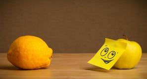 Apple avec la note de post-it regardant le citron images stock