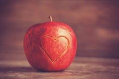 Apple avec un coeur a coupé en lui Photos stock