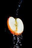 Apple bajo gotas del agua Fotos de archivo