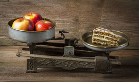 Apple in balance. With cake on wooden background Royalty Free Stock Image