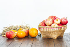Apple in bamboo basket and oranges on wooden table Royalty Free Stock Photo