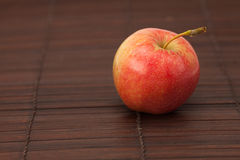 Apple on bamboo mat Stock Image