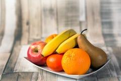 Apple, banan, russet, orange, mandarin,plate. Apple banan russet orange mandarin plate on the table royalty free stock photography