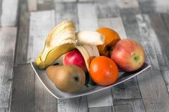 Apple, banan, russet, orange, mandarin,plate. Apple banan russet orange mandarin plate on the table royalty free stock photos