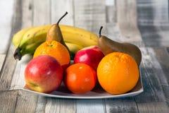 Apple, banan, russet, orange, mandarin,plate. Apple banan russet orange mandarin plate on the table stock photos