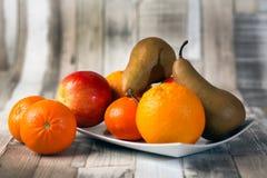 Apple, banan, russet, orange, mandarin plate. Apple banan russet orange mandarin plate on the table royalty free stock image