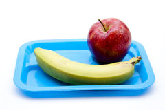 Apple and banana on blue plate Royalty Free Stock Photos
