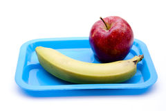 Apple and banana on blue plate. And on white background Royalty Free Stock Photography