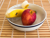Apple and banana inside bowl on wooden stripes table. Healthy eating, fresh apple and peeled banana inside bowl on wooden stripes table Royalty Free Stock Photos