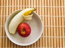 Apple and banana inside bowl on wooden table. Healthy eating, fresh apple and peeled banana inside bowl on wooden table Royalty Free Stock Images
