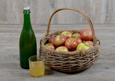 Apple basket and bottle with a glass cider Royalty Free Stock Photography