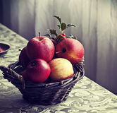 Apple basket on tablecloth Stock Image