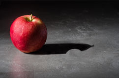 Apple with a bite in the shadow Stock Photo