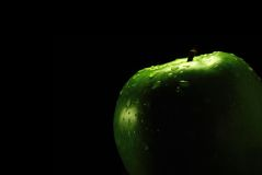 Apple and black. Green apple with drops on black background Royalty Free Stock Photography
