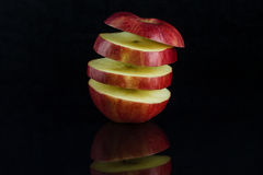 Apple on a black background. Apple cut into slices hanging in the air on a black background with reflection Royalty Free Stock Images