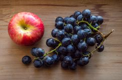 Apple And Black Grapes On Wood Background Stock Image