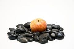 Apple on black stones Stock Photography