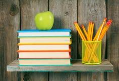 Apple, Bleistifte und Bücher auf einem hölzernen Regal Lizenzfreies Stockbild