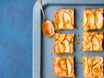Apple blonde brownies with caramel on tray blue background. Home made apple cinnamon blondies with salted caramel. Sweet food home made dessert treat. Dark blue stock images