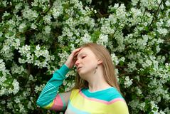 Apple bloom allergy. Young woman suffers from allergies against the backdrop of a blossoming apple tree stock photos