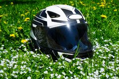 The helmet lies on a blooming meadow. On summer royalty free stock photography