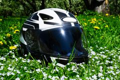 The helmet lies on a blooming meadow. On summer stock images