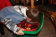 Apple bobbing. Is a game often played on Halloween. The boy in the picture is trying to catch an apple using his teeth. Use of hands is not allowed in this game stock photo