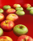 Apple bobbing. During the harvest season in a red tub of water Stock Photo