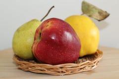 Apple, bonkreta i pigwa na słomianym talerzu, zdjęcie stock