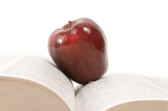 Apple on Book. Macintosh red apple resting on a large open book Royalty Free Stock Photo