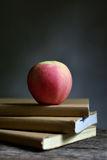 Apple on book and black background. Royalty Free Stock Photography