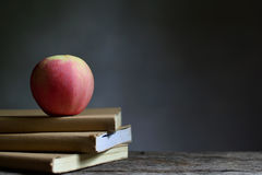 Apple on book and black background. Royalty Free Stock Images