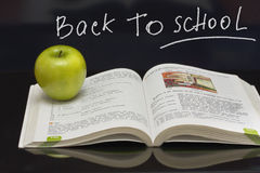 Apple on the  book. Blackboard with sign. A green apple on the  schoolbook Royalty Free Stock Photography