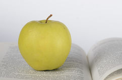 Apple on the book. Green apple on the page of opened book on white background Royalty Free Stock Photography