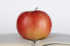 Apple on the book. Apple on the pageg of opened book on white background Stock Images