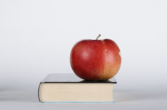 Apple on the book. Red apple on the closed book on white background Royalty Free Stock Image