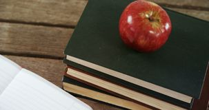 Apple on book stack 4k. Close-up of apple on book stack 4k stock footage