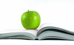 Apple on a book on white Stock Photography