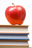 Apple on Books. Red apple on a stack of books on a white background Royalty Free Stock Photography