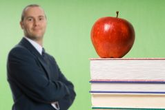 Apple on books. Apple sitting on top of books in a classroom stock image
