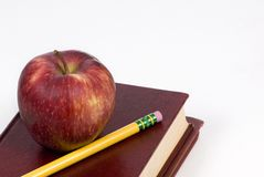 Apple and books. A pile of shcool books with an apple and pencil on top Royalty Free Stock Images