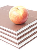 Apple on books. Isolated apple on a stack of four books Royalty Free Stock Image