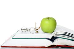 Apple with books. Image of a green apple sitting on a stack of books Stock Image