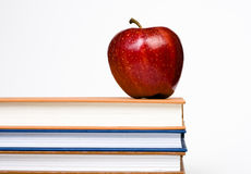 Apple on Books. Red apple on a stack of books on a white background Royalty Free Stock Images