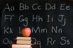 Apple, books, alphabet: education. Apple, textbooks with alphabet written on blackboard in background Stock Photo