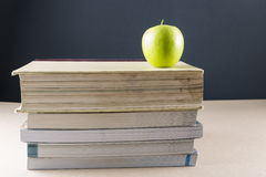 Apple on books. Apples on a pile of books on a table with black background Royalty Free Stock Photo