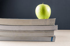 Apple on books. Apples on a pile of books on a table with black background Royalty Free Stock Image